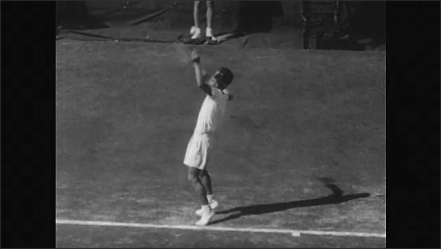 1950s: Herbert Flam and Art Larsen play tennis in front of audience. Flam serves, Larsen lobs ball over his head.