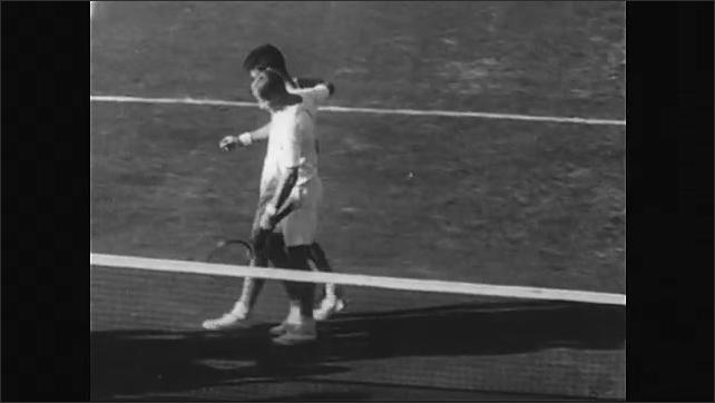 1950s: Herbert Flam and Art Larsen play tennis in front of audience. Crowd applauds. Larsen puts arm around Flam, they walk across court. Larsen receives trophy. Theodore Roosevelt in living room.