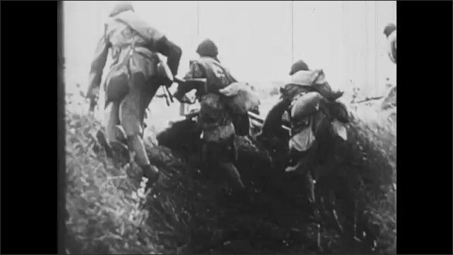 1940s: Smoke rises from building in city hit by bomb. Soldiers hiding behind hill as bomb explodes in trees nearby. Soldiers climb over embankment. Mussolini shouts from balcony to crowd below.