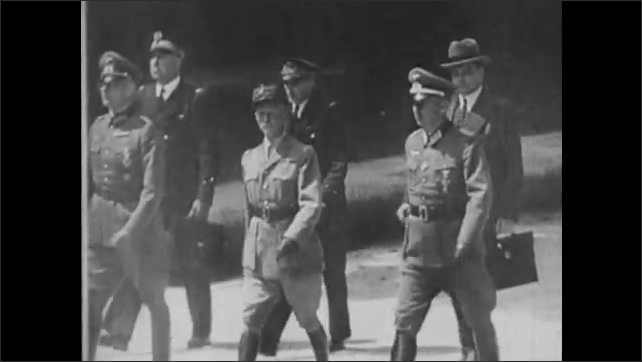 1940s: Nazi soldiers sit down around table in train car. French generals walk across courtyard and board train. On train French generals meet with Nazi generals for surrender.