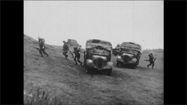 1940s: Soldier looks through binoculars. Artillery gun fires. Soldiers running. Soldiers get in small armored vehicles. Soldiers unload from trucks. Gun fires. Soldiers run. Fighter planes swarm.