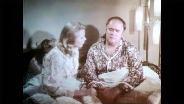1970s: Close up of woman. Man and woman talking in bed.