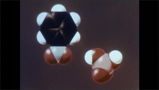 """1960s: Animation.  Molecule is labelled """"BENZENE.""""  Molecules split into pieces and form new combinations.  Text reads """"SULFURIC ACID"""" and """"NITROBENZENE."""""""
