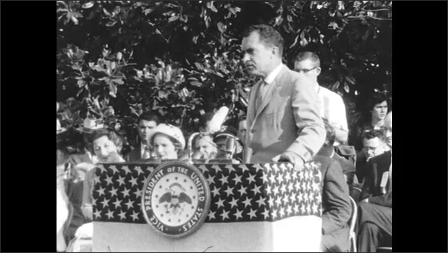 Lady in Audience Takes Photo as Nixon Speaks to Public