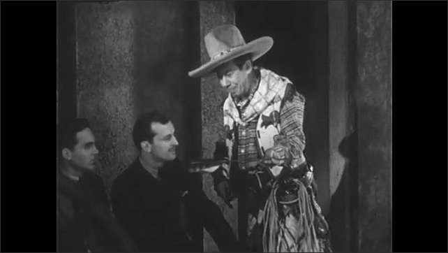 1930s: Cowboy speaks to man. Cowboy grimaces and pulls arrow out of his backside. Cowboy draws gun and approaches shadowy doorway. Child emerges.