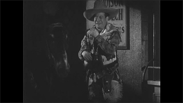 1940s: Sheriff laughs, points to himself. Man in suit and hat in bank laughs with sheriff, they gesture with hands. Sheriff exits bank, laughs and talks to horse excitedly.
