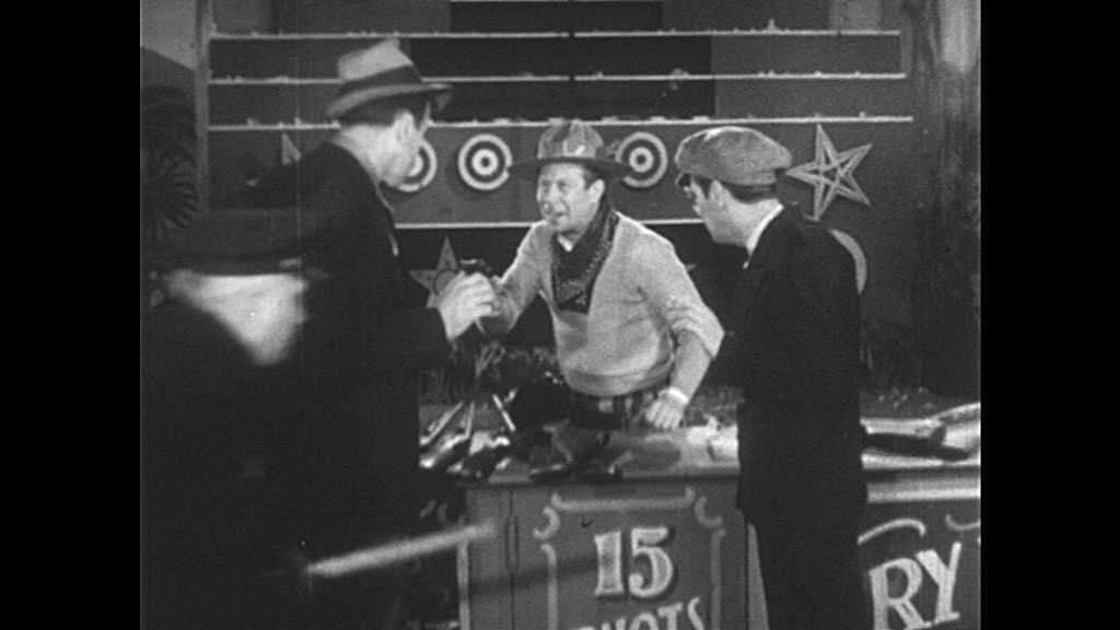 1930s: Man points gun at bank robbers as police officers grab them by the shoulders. Man speaks to police officers and gestures. Bank robber speaks to man.