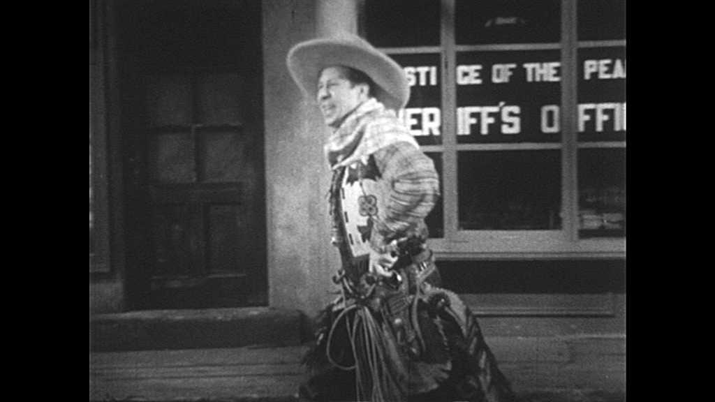 1930s: Cowboy stands in front of mirror, gestures and speaks. Cowboy shoots mirror, smiles, speaks and walks away.