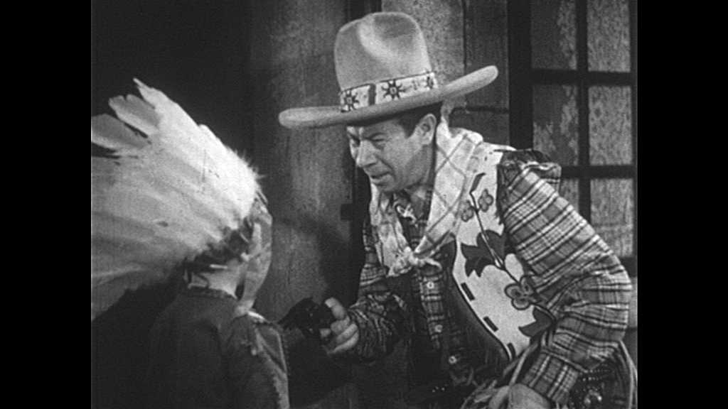 1930s: Cowboy speaks to child dressed as Indian. Child raises hand and speaks, then pats hand on mouth. Child shakes head.