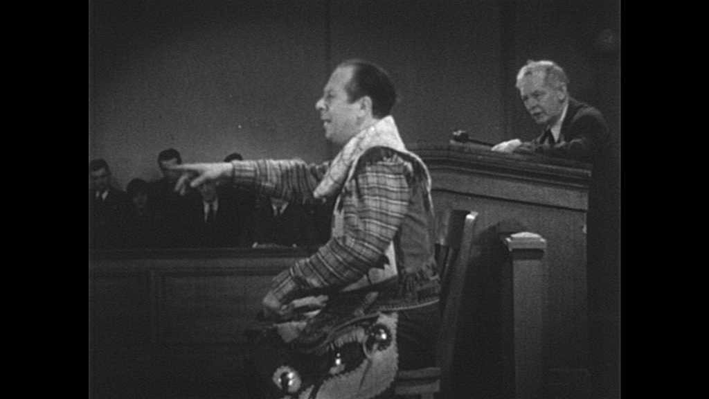 1940s: Man in suit approaches sheriff at witness stand as judge watches. Men speak as man in suit pushes gun in pocket to side of sheriff. Men speak, judge replies.
