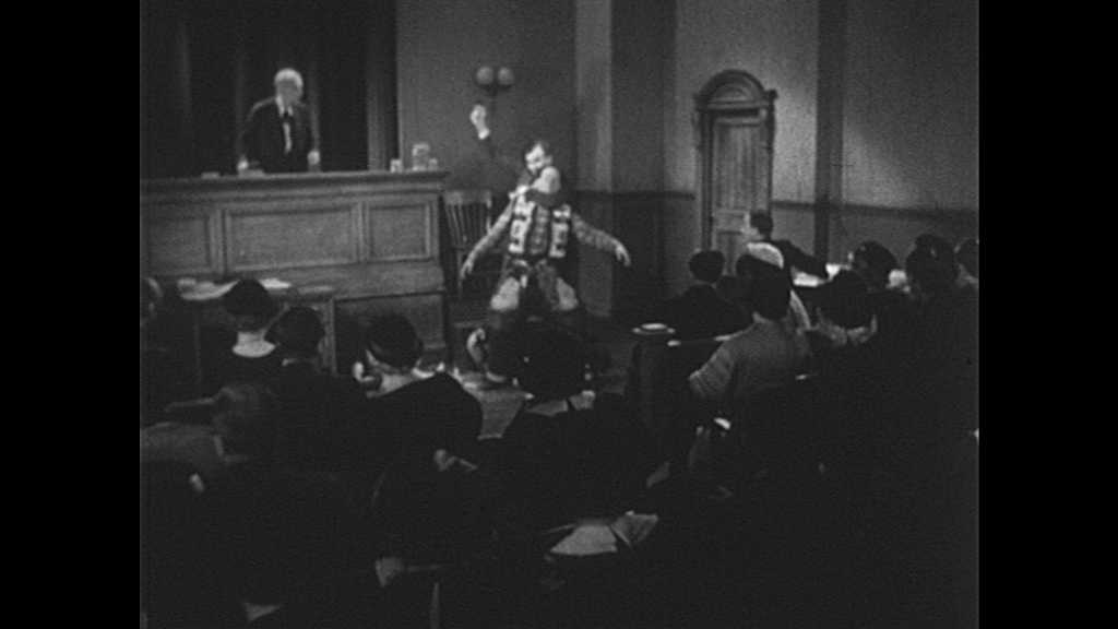 1940s: Man in courtroom pulls sheriff by neck out door, gun pointed out as jury, audience, and judge watch. Crowd storms door. Man points gun at sheriff by door, sheriff smiles and speaks with man.