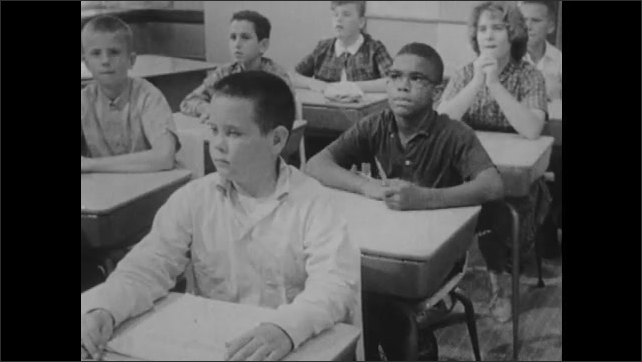 """1960s: Children sit at desks. Teacher puts """"we are testing"""" sign on door and hands out test."""