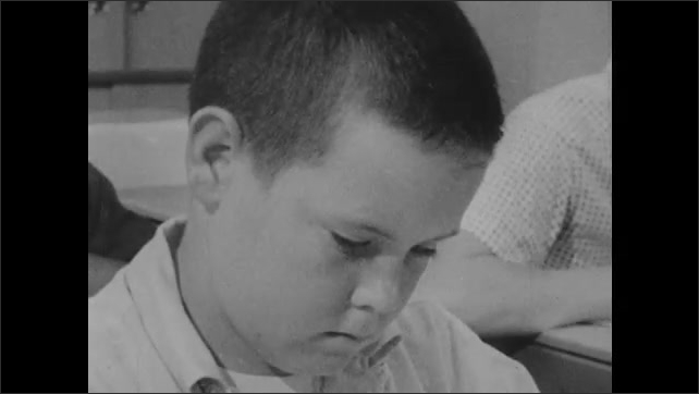 1960s: Children fill in bubbles on test. Teacher helps student.
