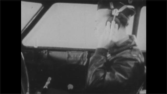1960s: Pilots check readings on instrument panel. Instrument comprehension booklet opens.