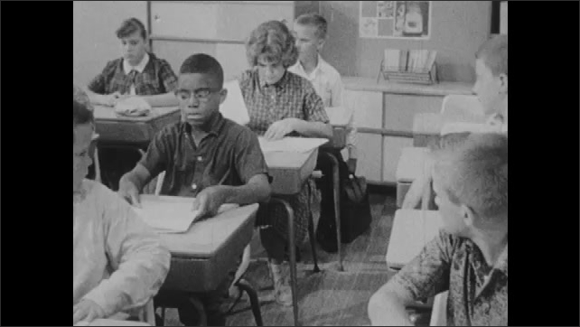 1960s: Children pass completed tests to front of class.