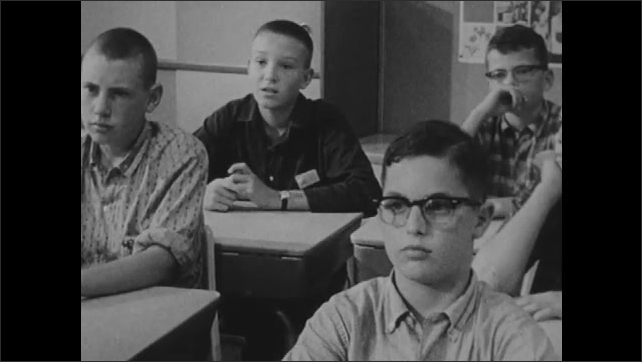 1960s:  teenage boys sit at desks and look forward in school classroom as boy with buzz cut and wristwatch raises hand and talks near bulletin board.