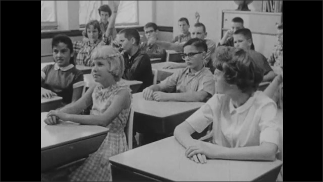 1960s: girl in seat talks as boys and girls sit in desks and raise hands in school classroom. man in suit pokes lip with stick near map of world. young lady chats while boy in eyeglasses waves arm.