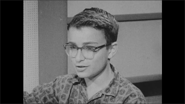 1960s: boy with eyeglasses talks, laughs, listens, responds and sits near shelves in office. hand holds analog stopwatch. woman stares.