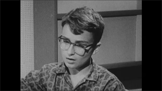 1960s: reels of audio tapes roll on tape recorder. woman looks down and talks. boy with eyeglasses listens and responds and sits near shelves. lady in dress observes in office.