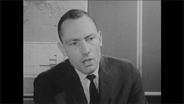 1960s: boy with buzz cut speaks as boys sit at desks and rub face with fingers in school. man in crew-cut and suit talks near world map. kid in shirt chats near bookcases in classroom.