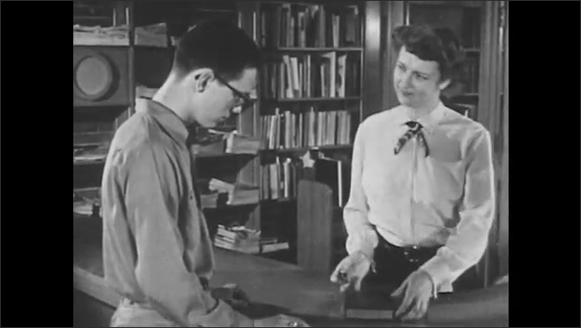1950s: Police officer talks to teenager. Girl pulls newspaper from shelf and opens it. Boy checks out book from librarian. Boy picks up magazines in busy library. Boy takes notes from magazine.