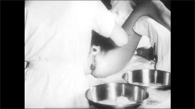 1950s: UNITED STATES: nurse washes vaginal opening before child birth. Nurse washes legs of lady