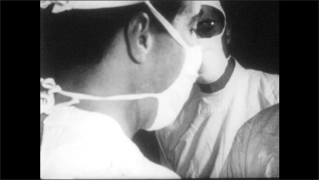 1950s: UNITED STATES: medic holds crying baby. Close up of medics in surgical masks. Placenta delivered.
