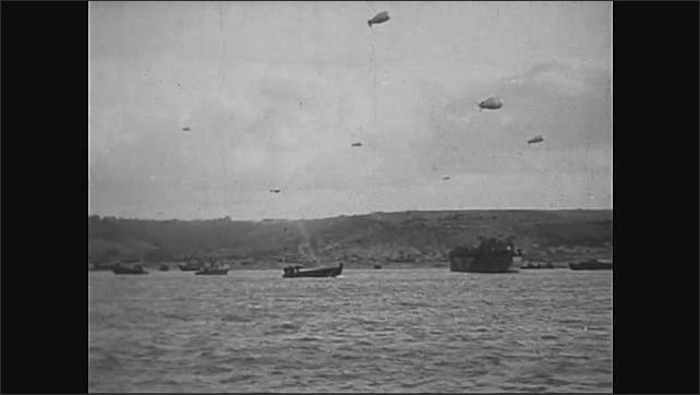 1940s: Normandy, Europe: tank drives across sand. Soldiers unload supplies. Soldiers wait on boats in day