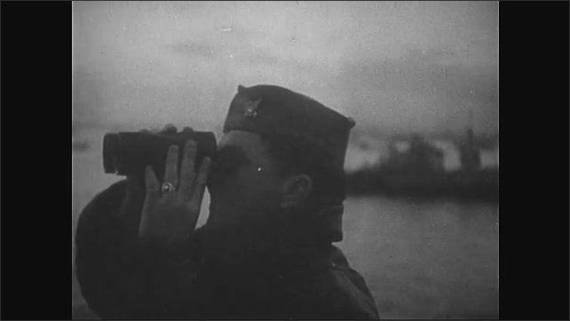 1940s: Normandy, Europe: artificial harbor looks after ships during bad weather. Waves crash against harbor wall. Soldier looks through binoculars.