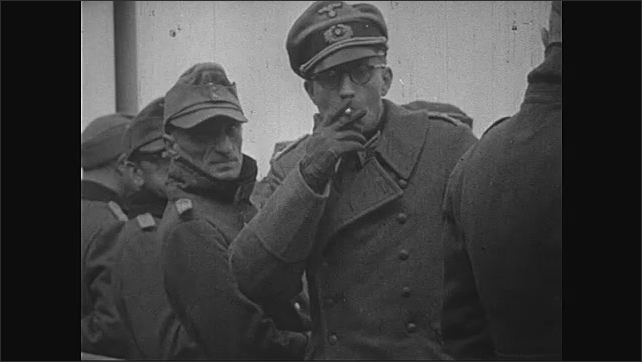 1940s: Normandy, Europe: German prisoner smokes cigarette. Soldier smokes pipe. German prisoners of war on deck of ship. Deck of ship from above