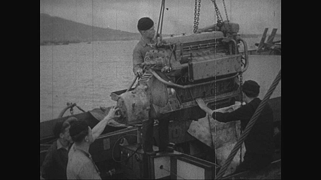 1940s: Men lower engine.  Welder.  Men work on boat.  Net holds boxes.  Text reads