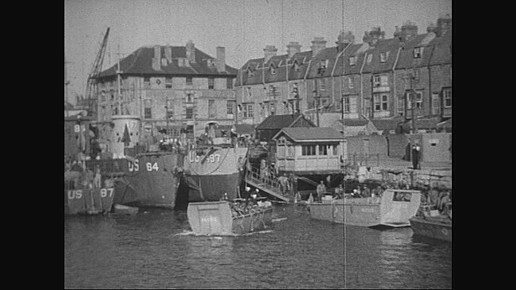 1940s: Village.  Boat transports soldiers.  Battleships.  Men on deck.