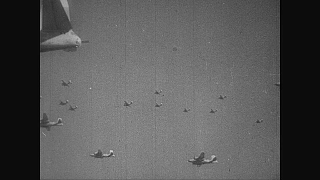 1940s: Airplanes.  Bombs explode.  Men.  Men kneel.  Priest speaks.