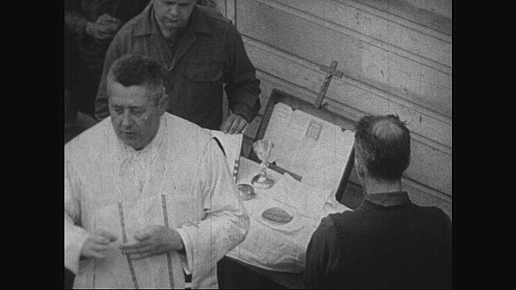 1940s: Priest gestures and speaks on deck of ship.  Men kneel.  Men stand.  Officer.