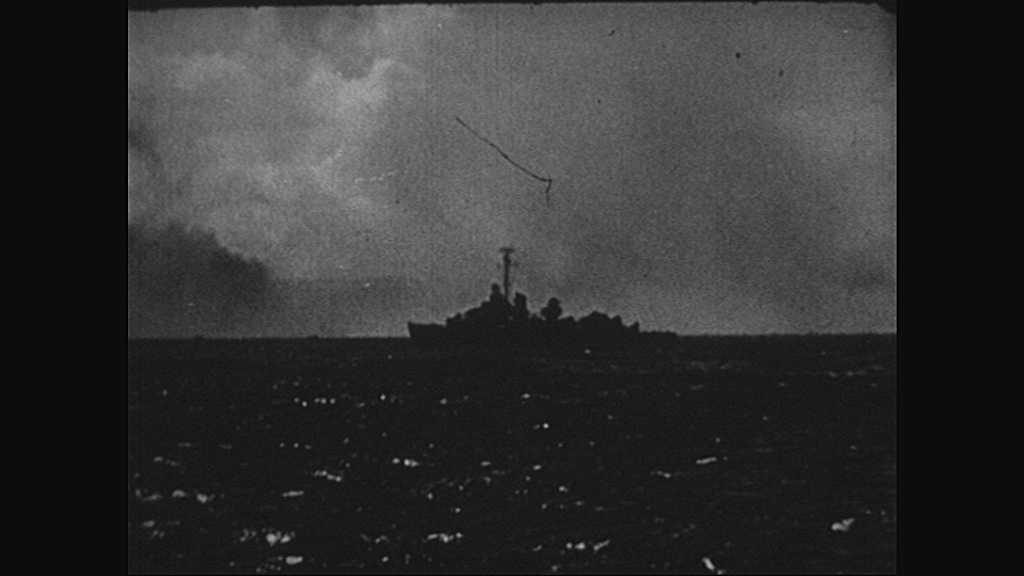1940s: Normandy, Europe: guns fire on ship. Bombs land in water by ship. Men climb down cargo nets on ship.