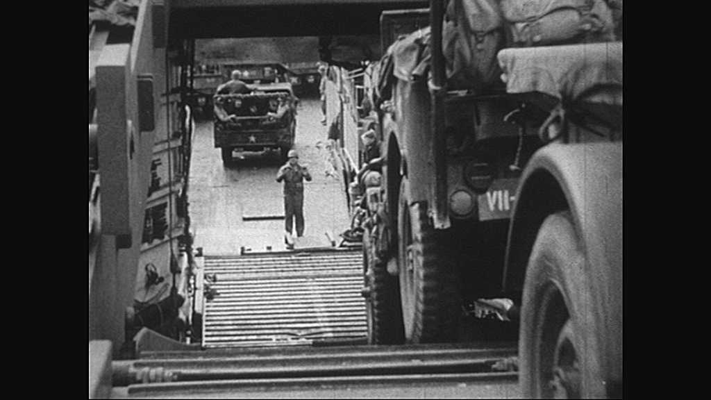 1940s: Normandy, Europe: tanks drive on to land. Rhino ferries transport supplies. Soldiers arrive on shore. Soldier speaks into radio
