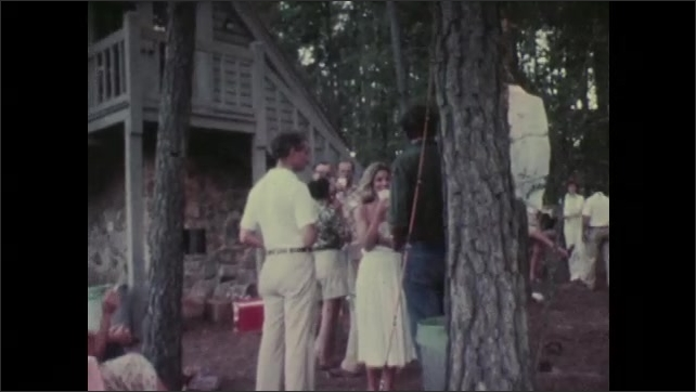 1970s: Band playing outside. Men talking. People socializing, people at table. People by covered area.