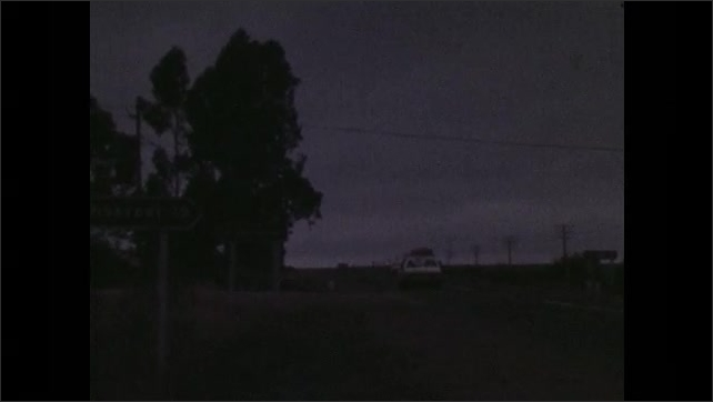1970s: Tracking shot from car, driving through city. View of highway. Car passes on road. Tracking shot, following truck on road. View of traffic sign.