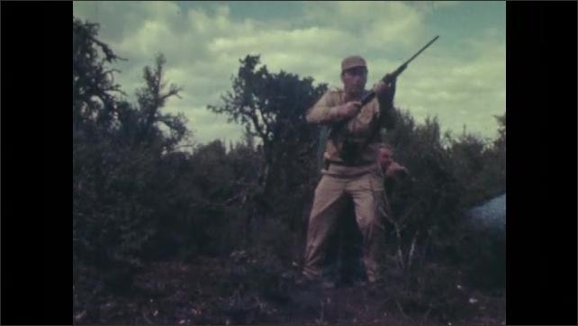 1970s: Long shot of antelope running. Man points, man fires gun. Long shot of antelope running. Men pick up dead antelope.