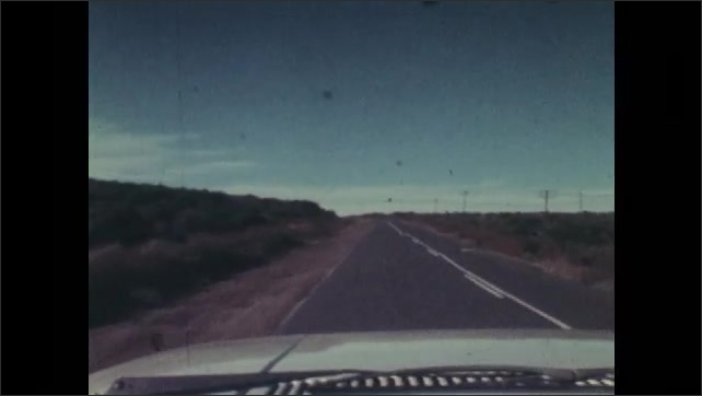 1970s: Men posing with dead antelope, men shake hands. Men get into car, man closes door, zoom out. Tracking shot from car, driving on road. View of horizon.