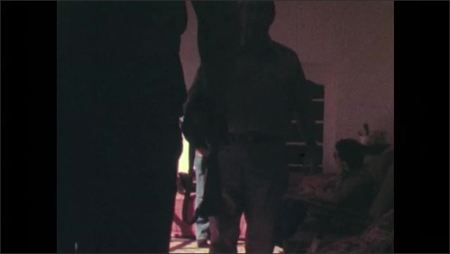 1970s: Rear of car, man enters house in background. Men shake hands in living room.