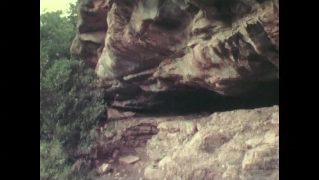 1970s: Antelope running in grass. Pan of antelope running. View of cave. View of cave paintings. Interior of cave.