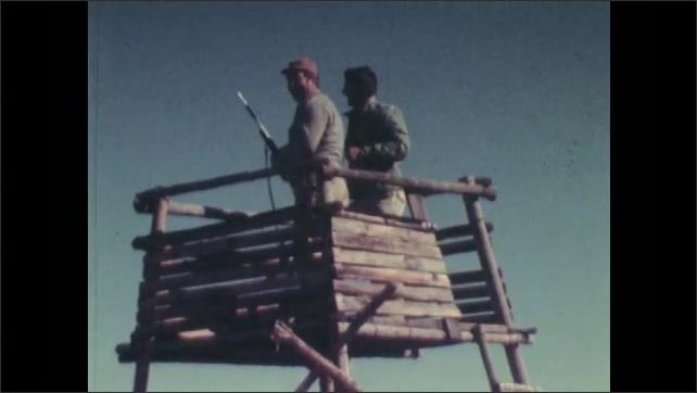1970s: Men in hunting tower, man fires gun, men stand. Men riding horses through brush.