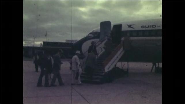 1970s: Shots of people boarding plane.