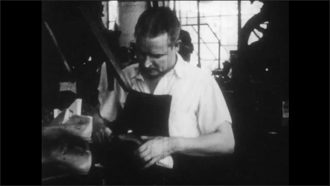 1950s: man with visor inspects and cuts leather hides at table with knife. man in apron swallows tacks and hammers together shoes on factory floor.