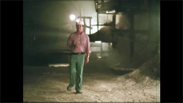 1980s: UNITED STATES: man stands inside repository. Man speaks to camera. Man wears hard hat. Rock salt quarry.