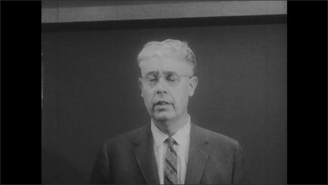 1950s: Man talks standing in front of chalkboard.