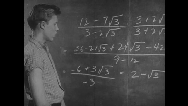 1950s: Boy and woman talk in classroom while looking at equations on chalkboard. Woman talks. Boy looks at equations then talks. Man talks standing in front of chalkboard.
