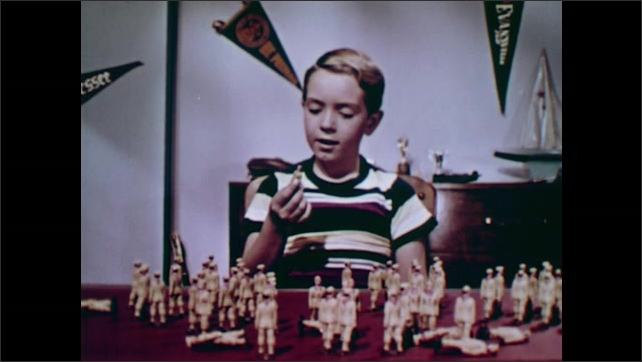 1950s: UNITED STATES: boy plays with toys on table. Boy talks to toy. Boy counts toy scouts.