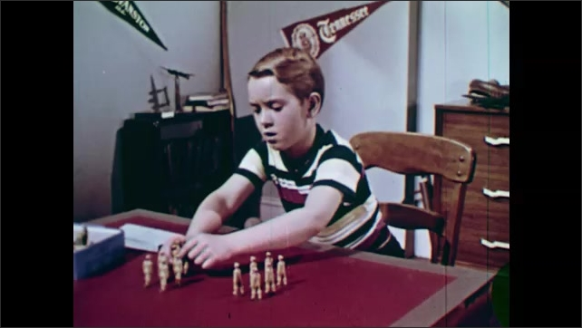 1950s: UNITED STATES: tens and units written on paper. Boy writes on paper. Boy keeps score on card. Boy tidies toys into box.